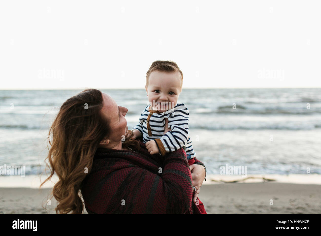 Mother on beach holding smiling baby boy - Stock Image