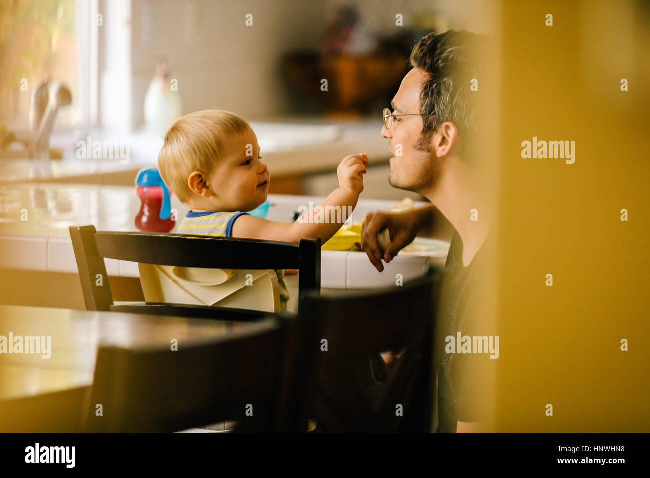 Father helping young son at meal time - Stock Image
