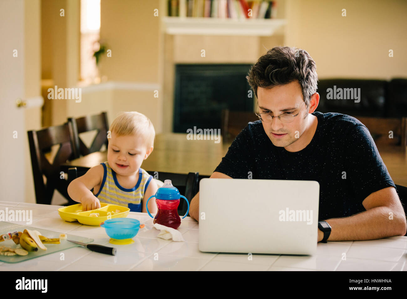 Father and young son sitting at table, son eating, father using laptop - Stock Image
