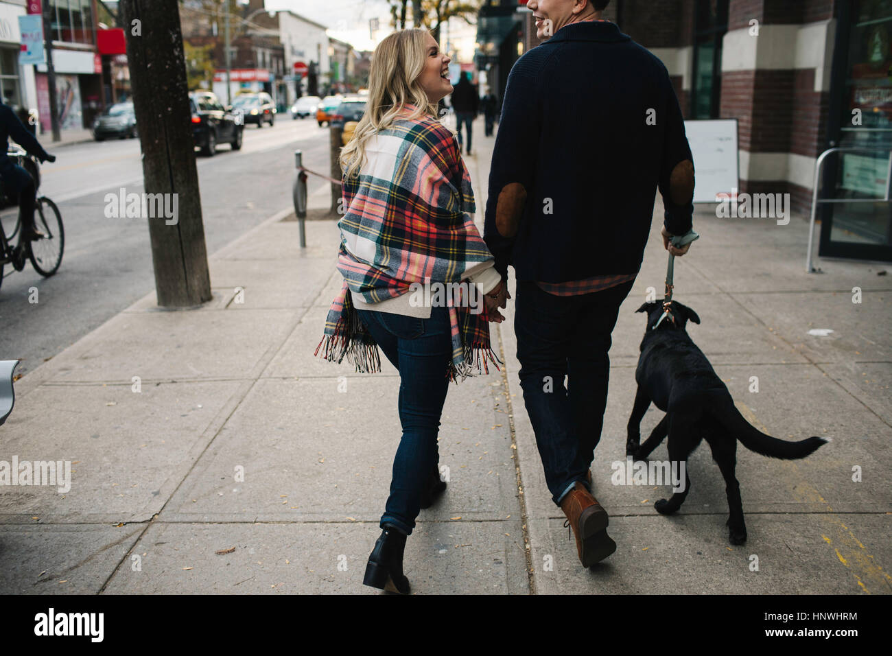 Young couple walking dog along street, rear view - Stock Image