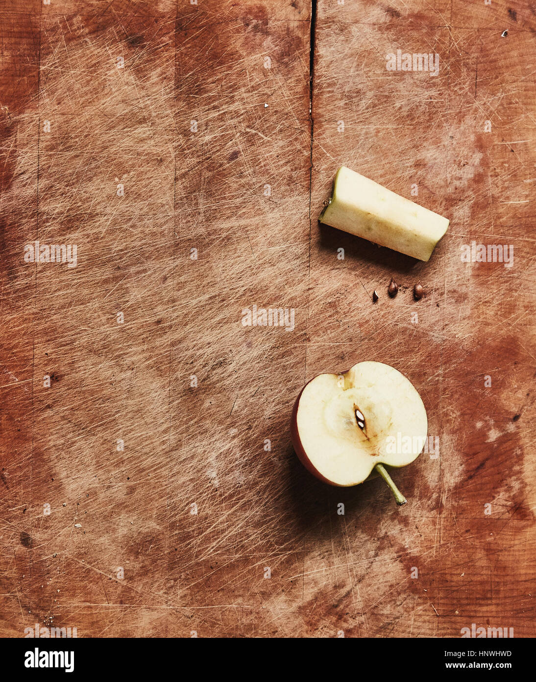Overhead view of fresh halved apple and apple core on wooden cutting board - Stock Image