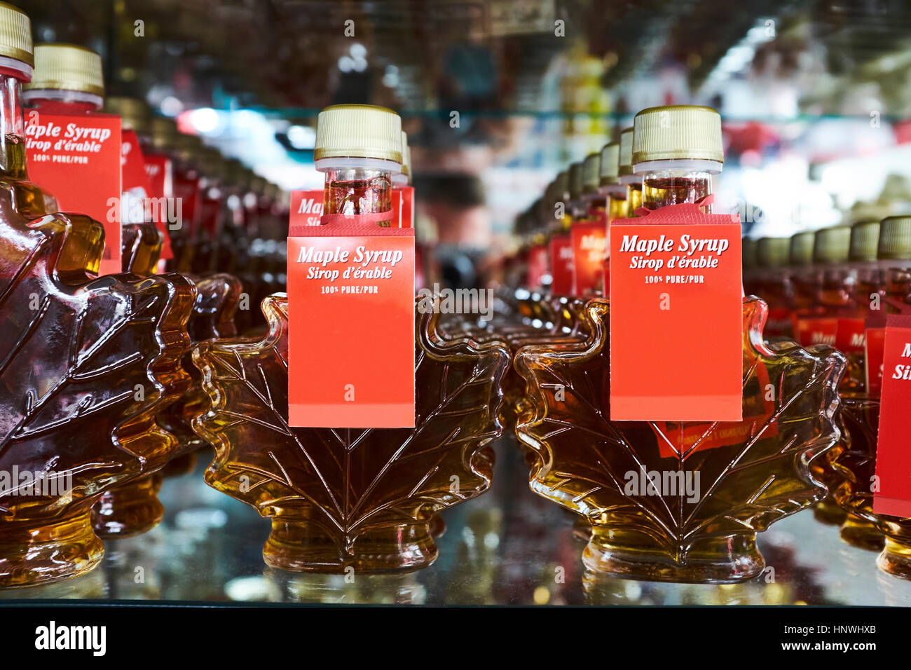 Rows of maple leaf shaped bottles containing maple syrup on shop shelf, Canada - Stock Image