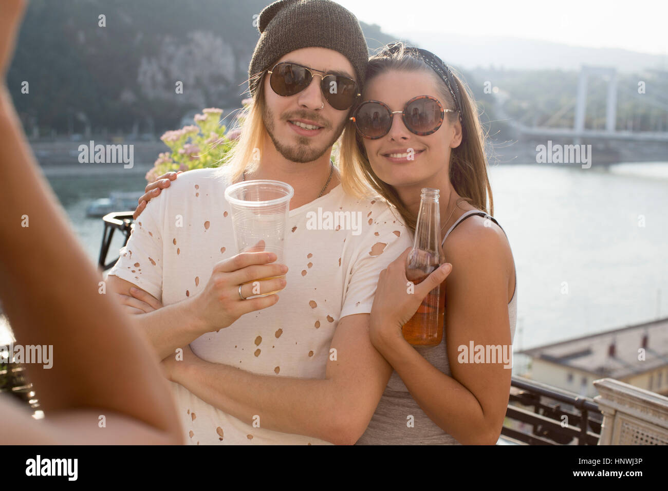 Young couple being photographed at roof terrace party, Budapest, Hungary - Stock Image
