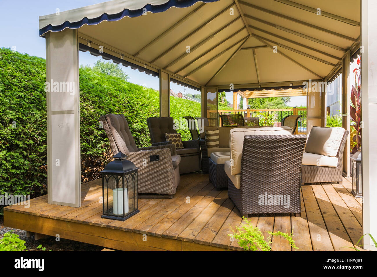 Gazebo on wooden deck furnished with wicker furniture, Quebec, Canada - Stock Image