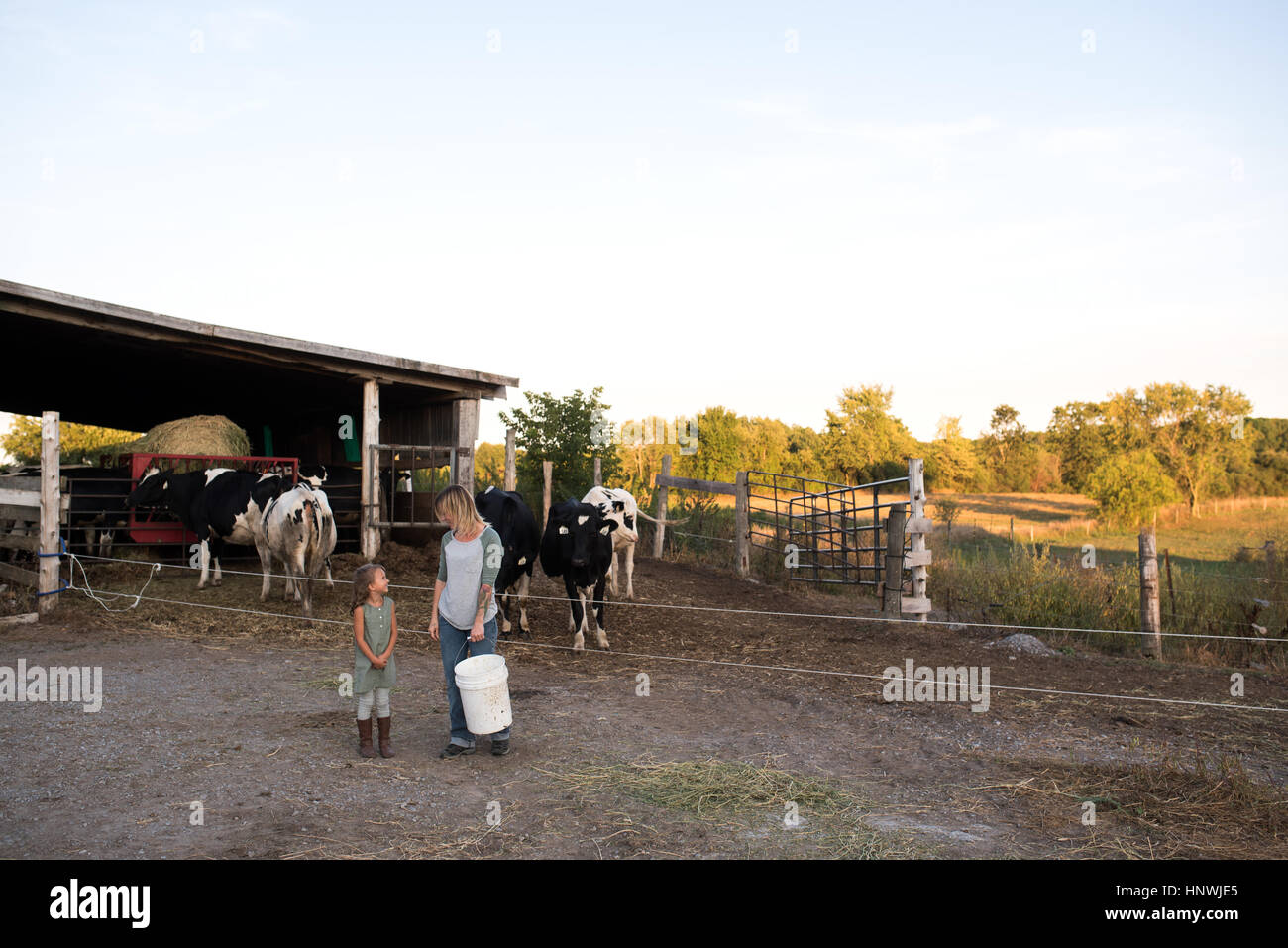 Mother and daughter standing together on farm, holding animal feed - Stock Image