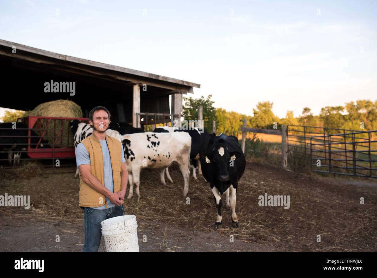 Portrait of farmer on farm, holding animal feed - Stock Image