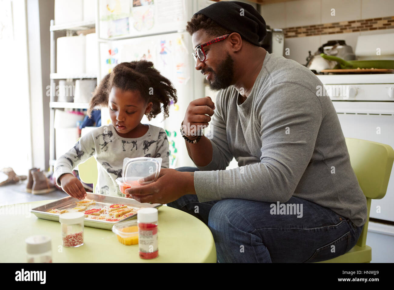 Father and daughter decorating unbaked cookies - Stock Image