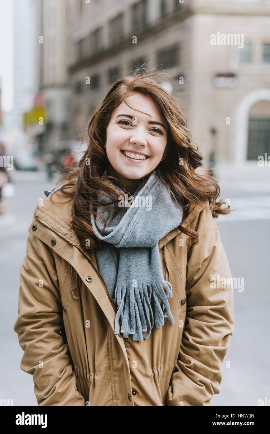 Portrait of young woman, smiling, outdoors - Stock Image