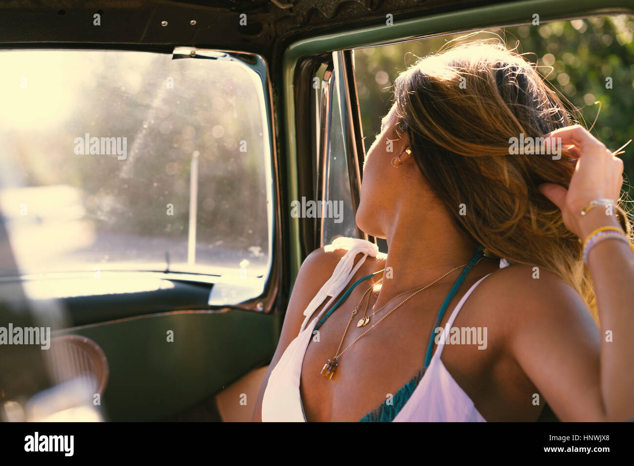 Young woman on road trip looking over her shoulder from parked truck - Stock Image