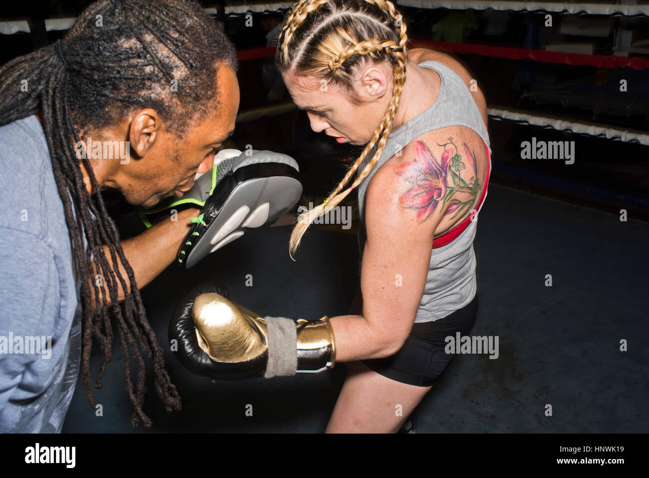 Female boxer punching trainer's boxing mitt in boxing ring - Stock Image