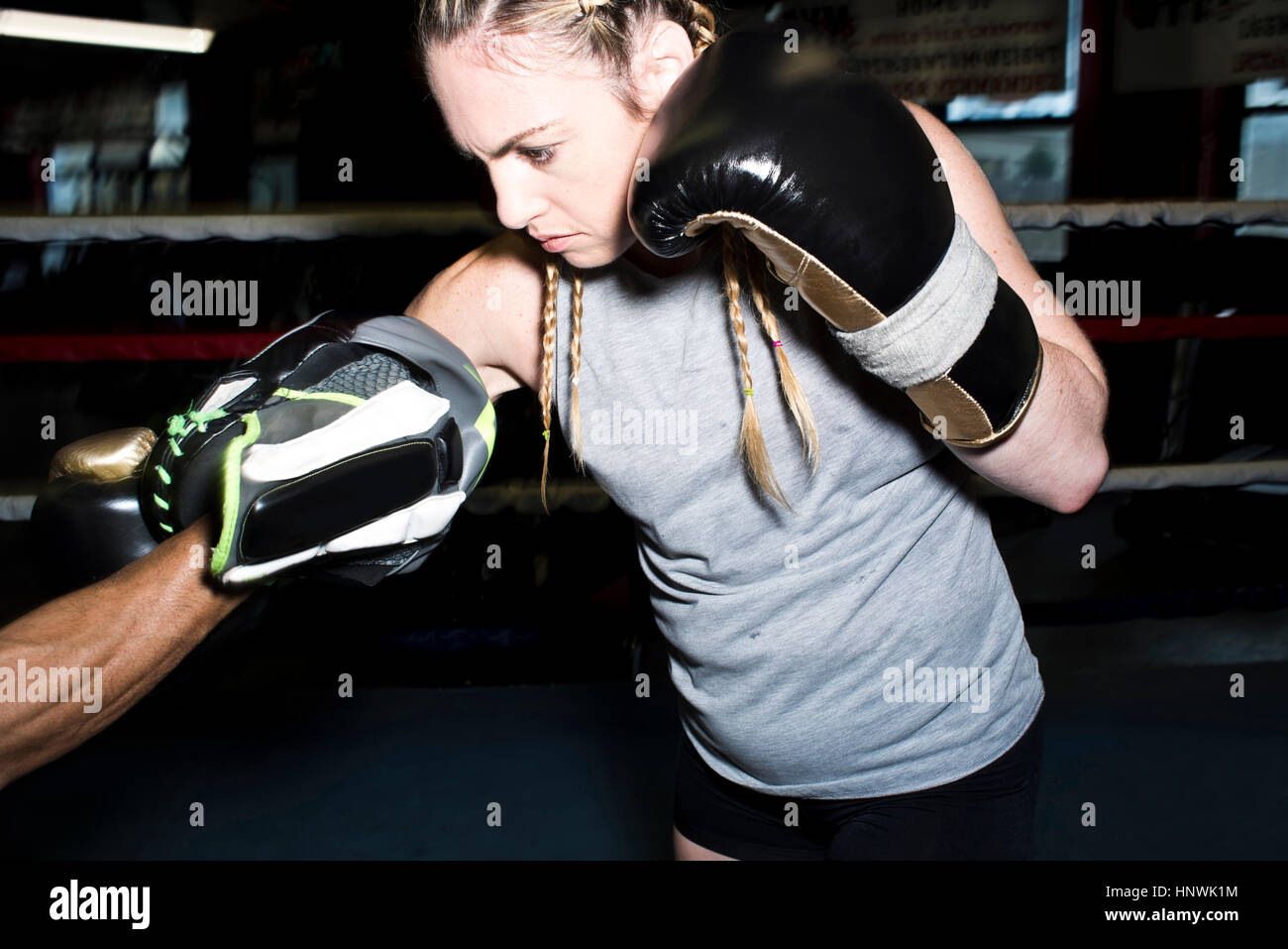 Female boxer punching her trainer's boxing mitt in boxing ring - Stock Image