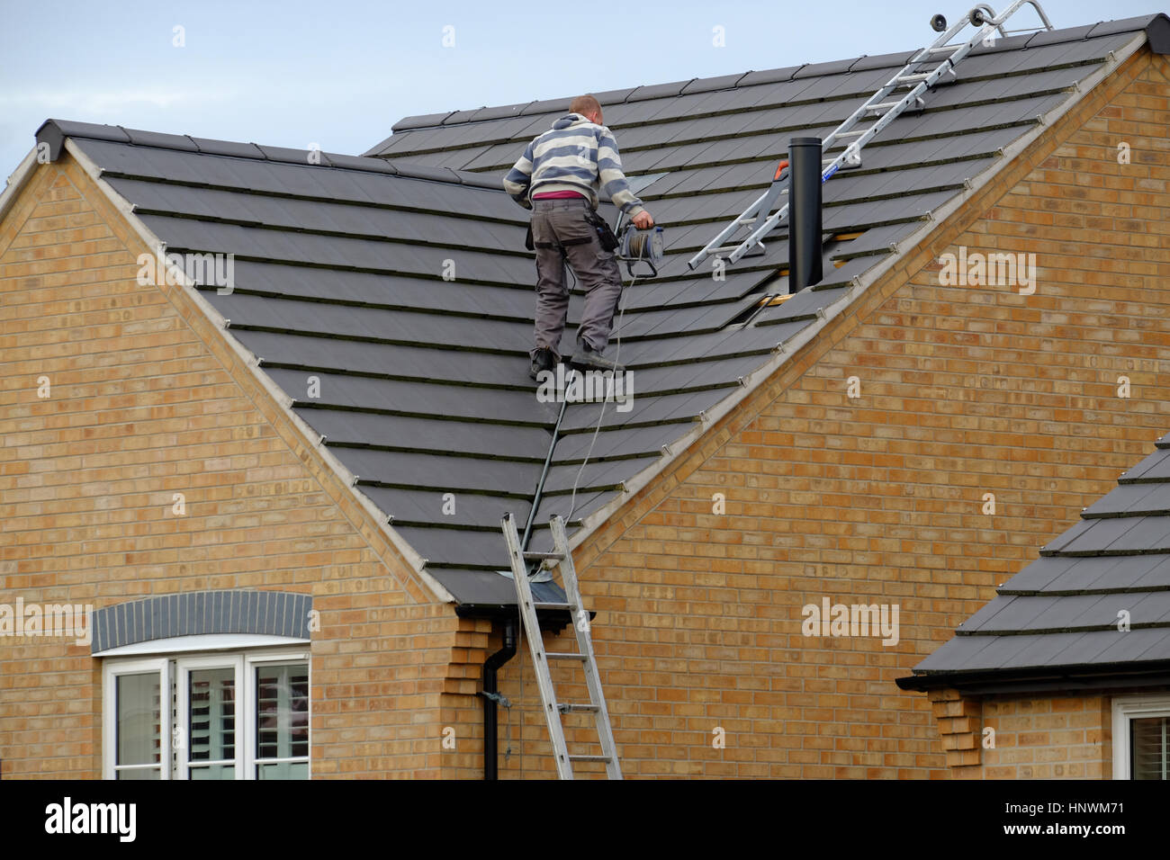 Workman on a house roof installing a chimney - Stock Image