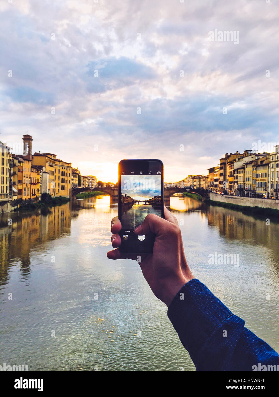 Man holding smartphone for take a photo during sunset - Stock Image