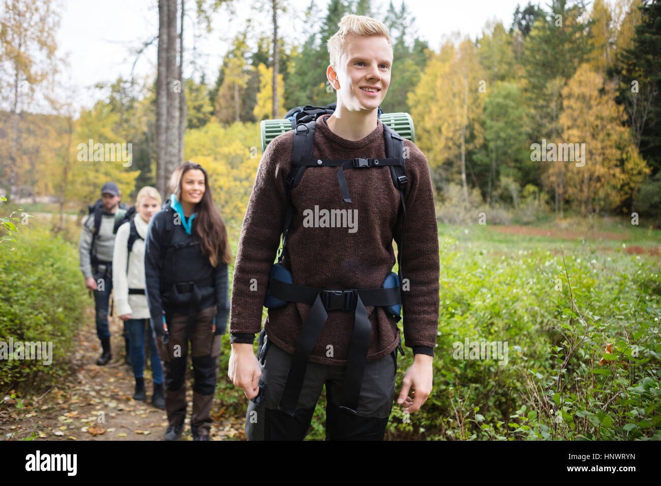Smiling Man With Friends Hiking On Forest Trail - Stock Image
