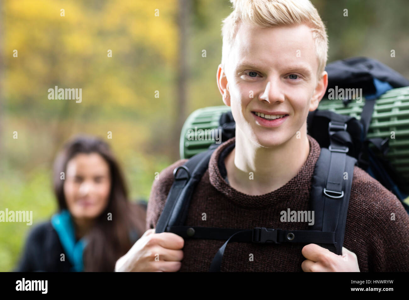Portrait Of Confident Male Hiker In Forest - Stock Image
