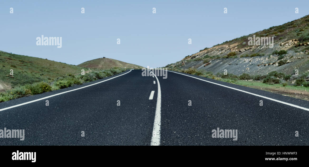 view of a lonely road in a rural landscape with no traffic - Stock Image