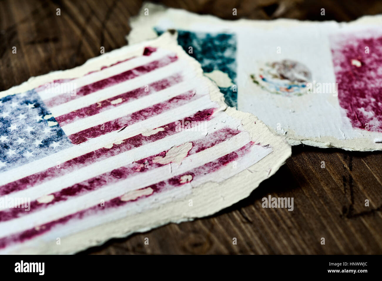 the flag of United States and the flag of Mexico in two aged pieces of paper on a rustic wooden background - Stock Image