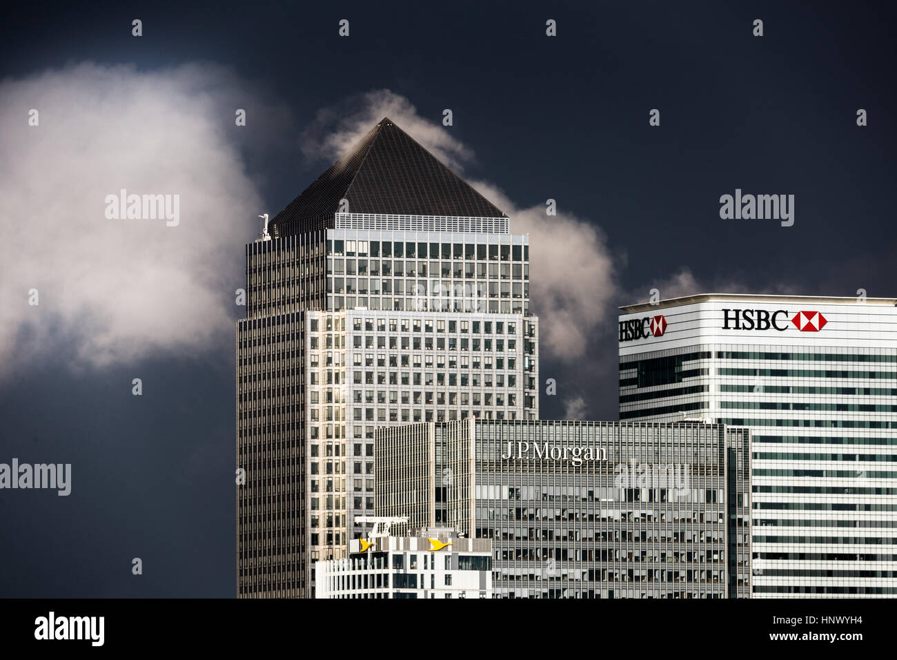 Steam and clouds over Canary Wharf business park buildings in London, UK. - Stock Image