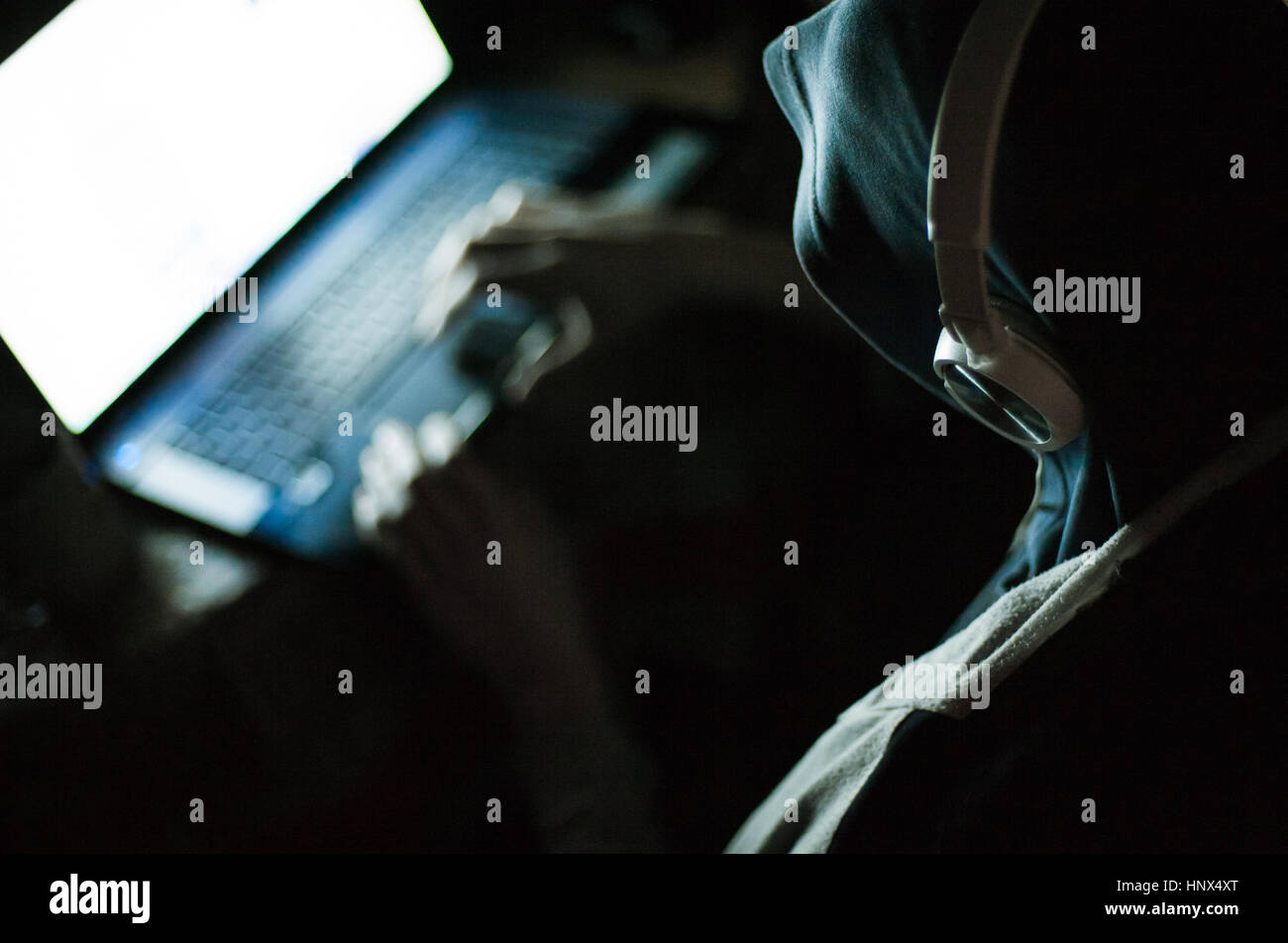 Man hacker in hood and headphones working on laptop in the dark - Stock Image