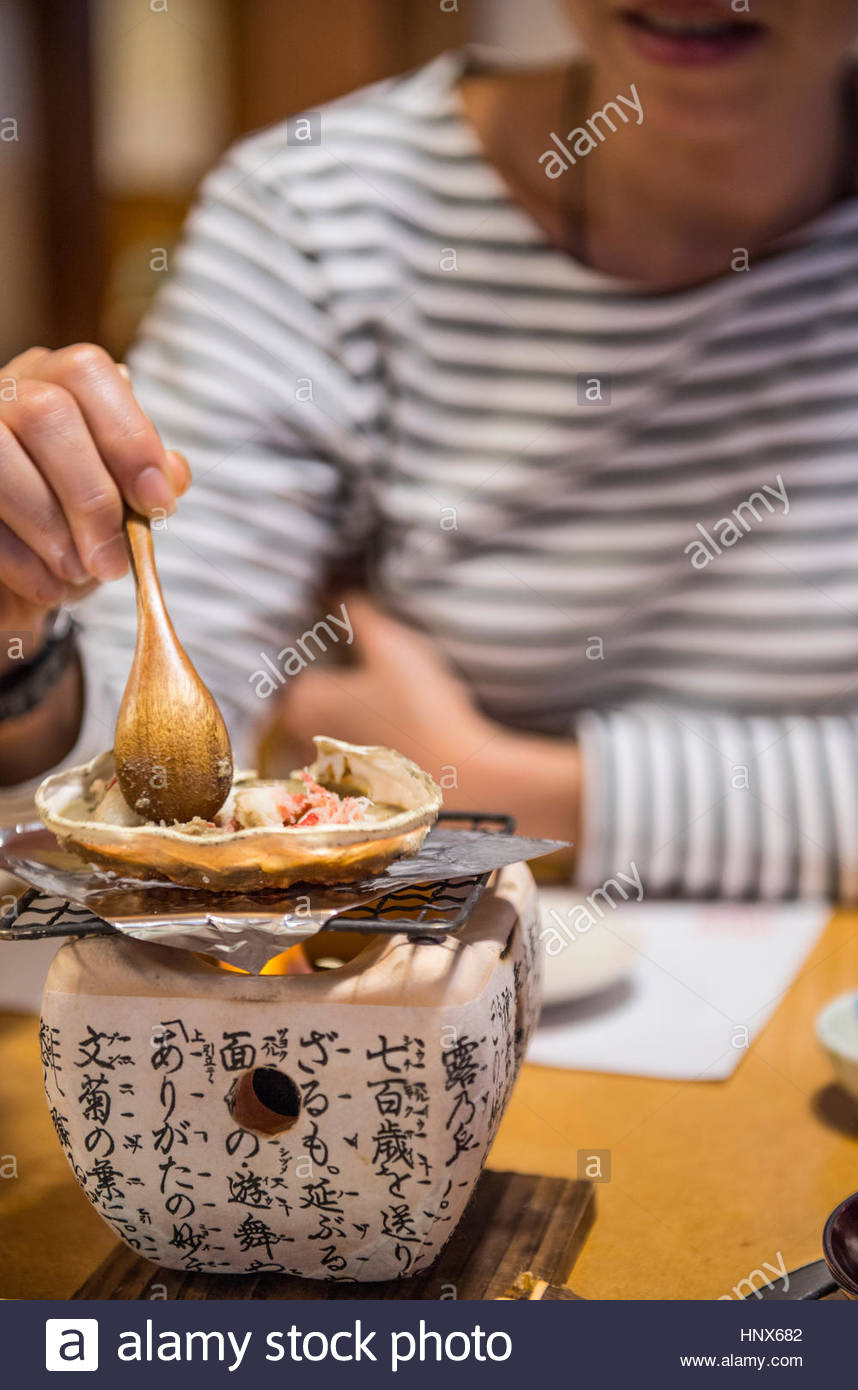Woman eating crab, cooked on a clay stove Kyoto, Japan - Stock Image
