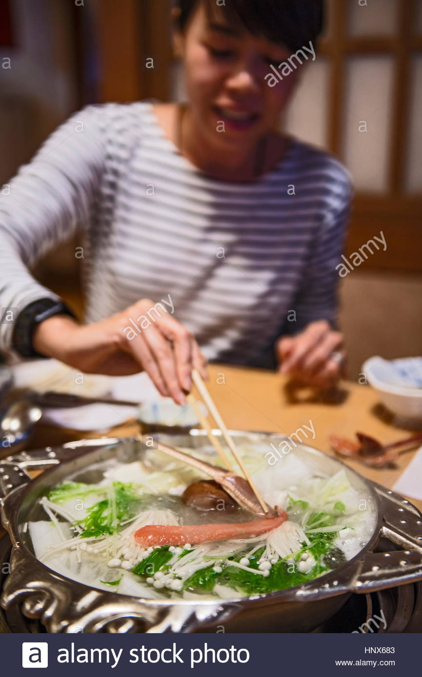 Woman eating crab with chopsticks, Kyoto, Japan - Stock Image