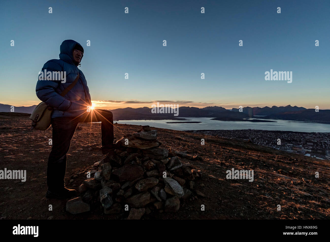 Man climbing a summit near Tromso in autumn, Arctic Norway - Stock Image