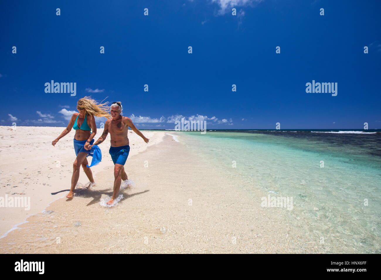 Mature couple walking along beach, holding hands, Ile aux Cerfs, Mauritius - Stock Image