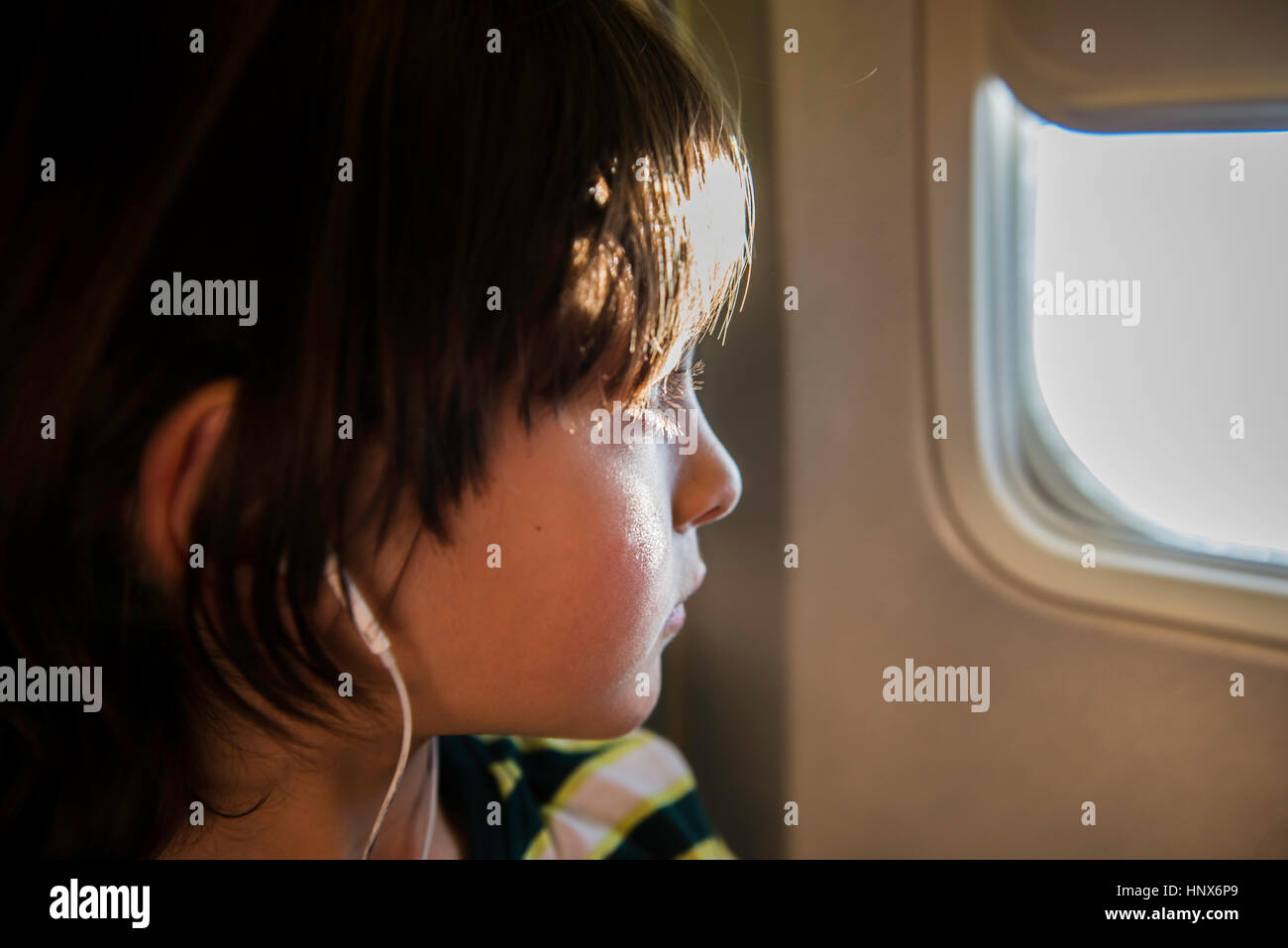 Boy on airplane looking through sunlit airplane window - Stock Image