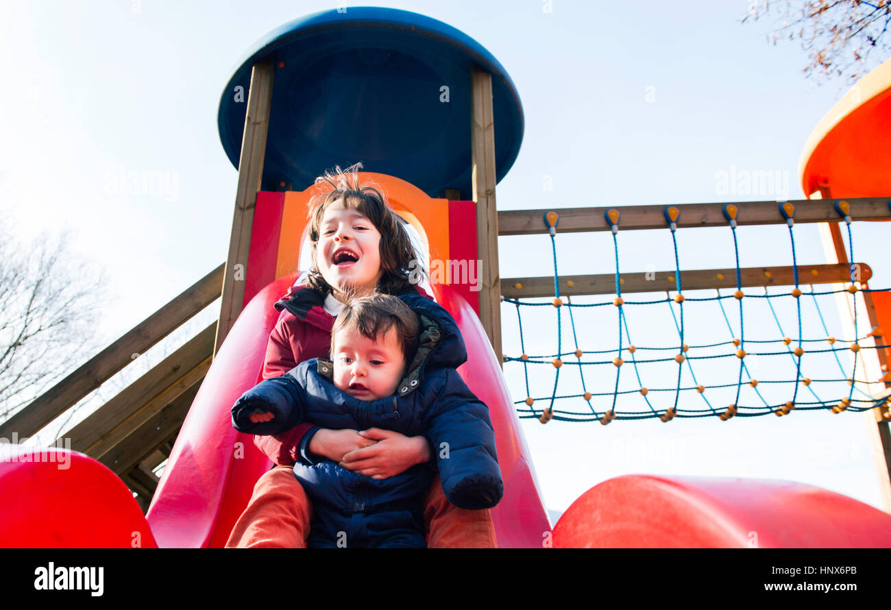Boy and baby brother sliding down playground slide - Stock Image