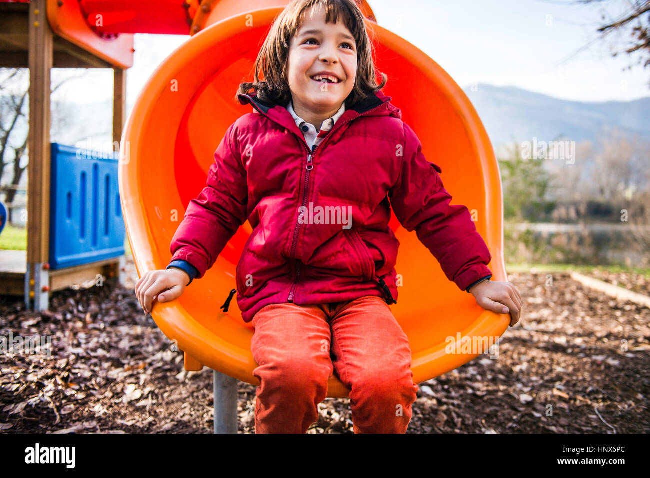 Boy sitting on orange playground slide - Stock Image