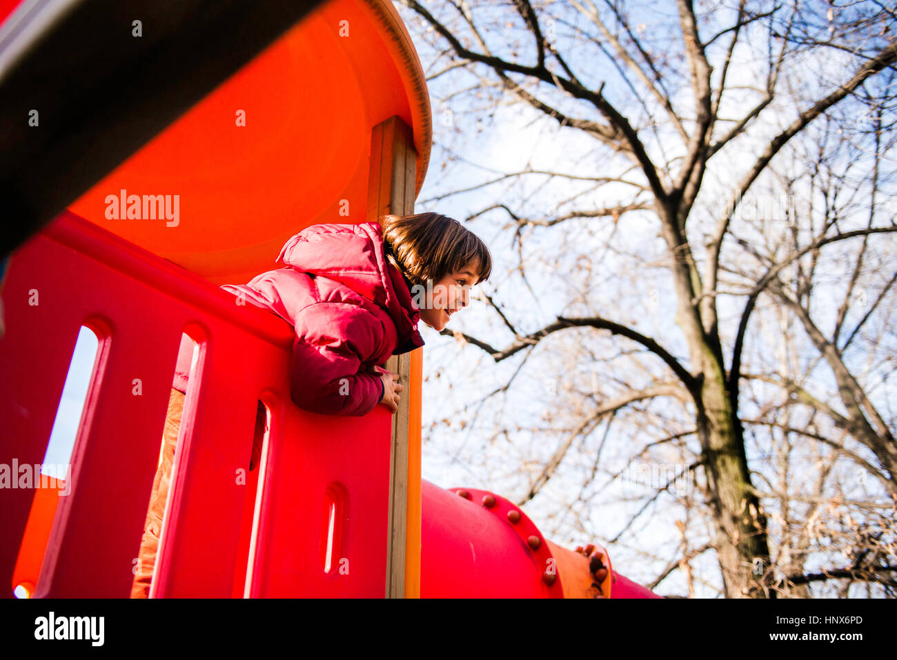 Boy looking out from top of red playground slide - Stock Image