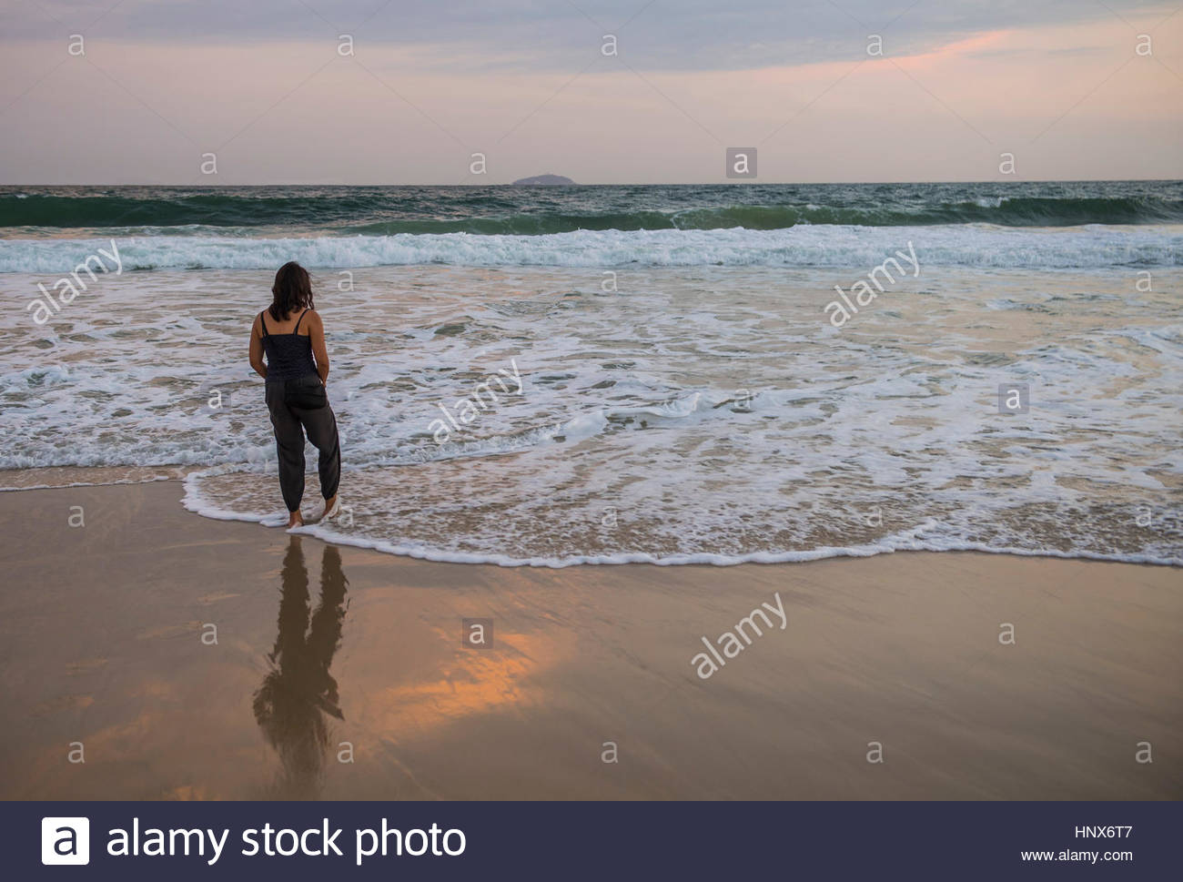 Woman paddling in lapping waves, Copacabana, Rio de Janeiro, Brazil - Stock Image