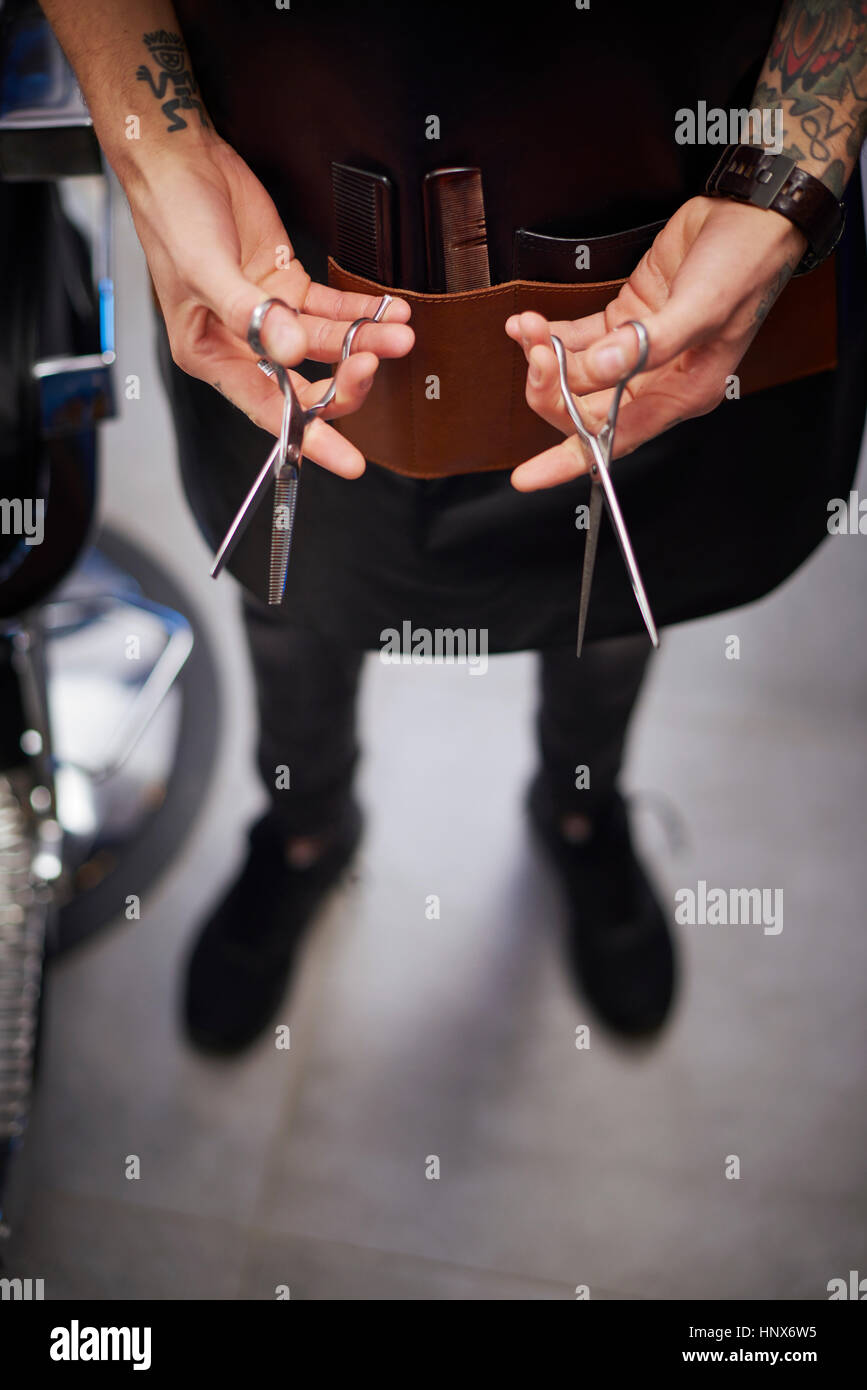 Hairdresser holding scissors - Stock Image
