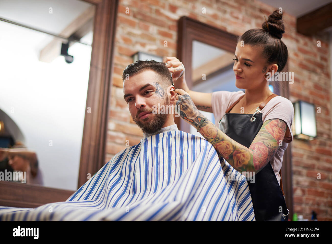 Hairdresser cutting customer's hair - Stock Image