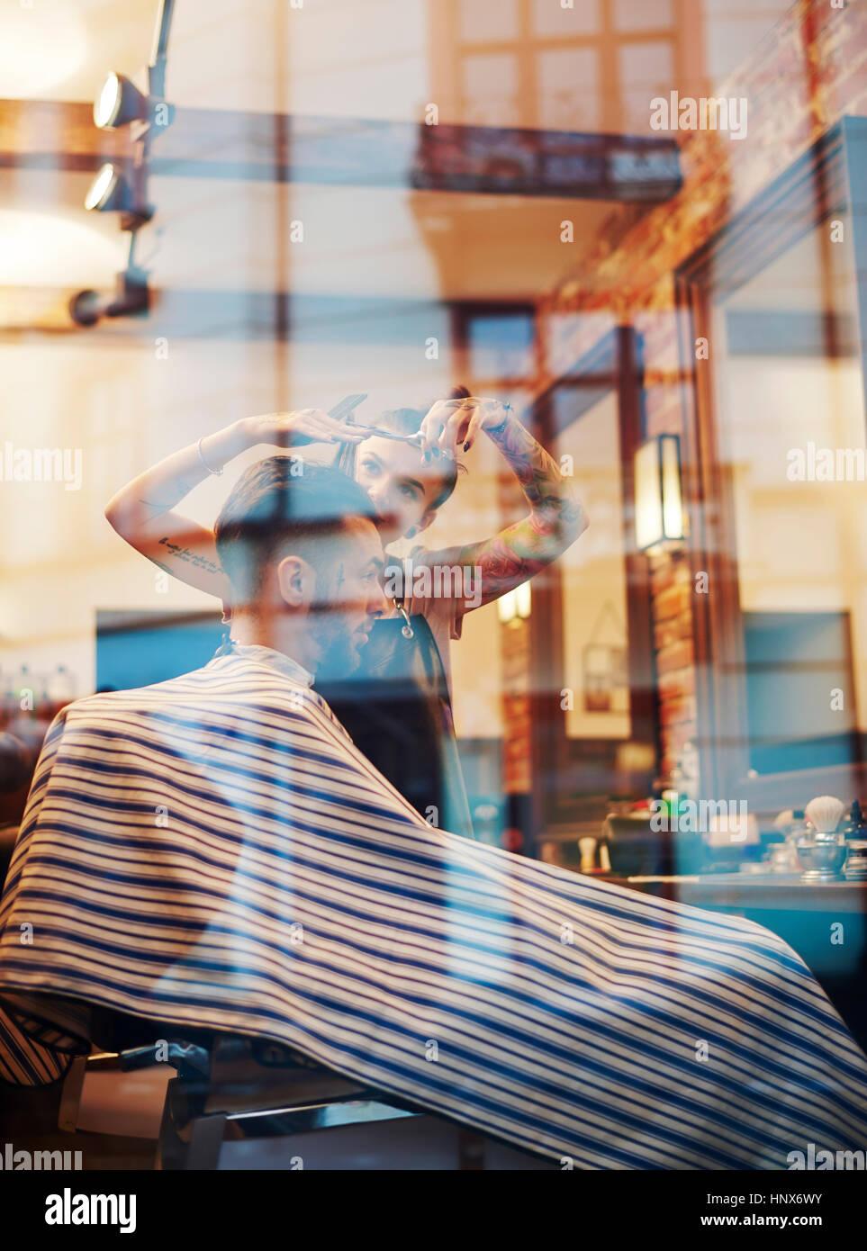 View through window of hairdresser cutting customer's hair Stock Photo