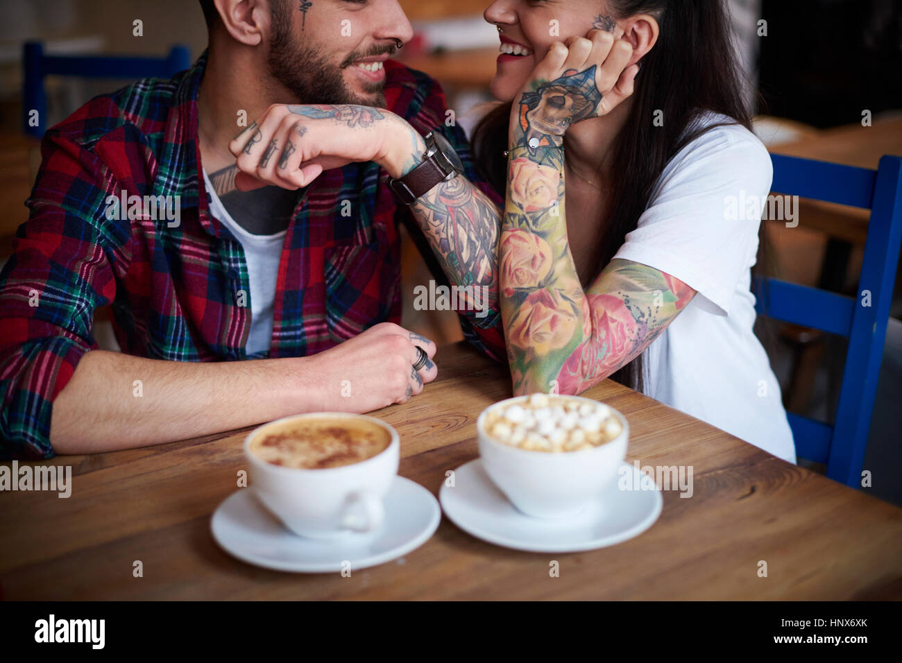 Couple in coffee shop face to face smiling - Stock Image