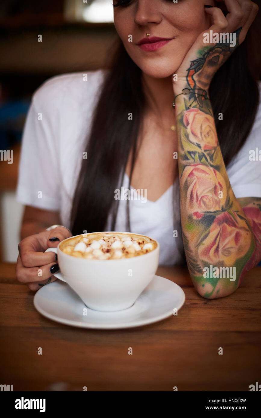 Tattooed woman with cup of hot chocolate - Stock Image