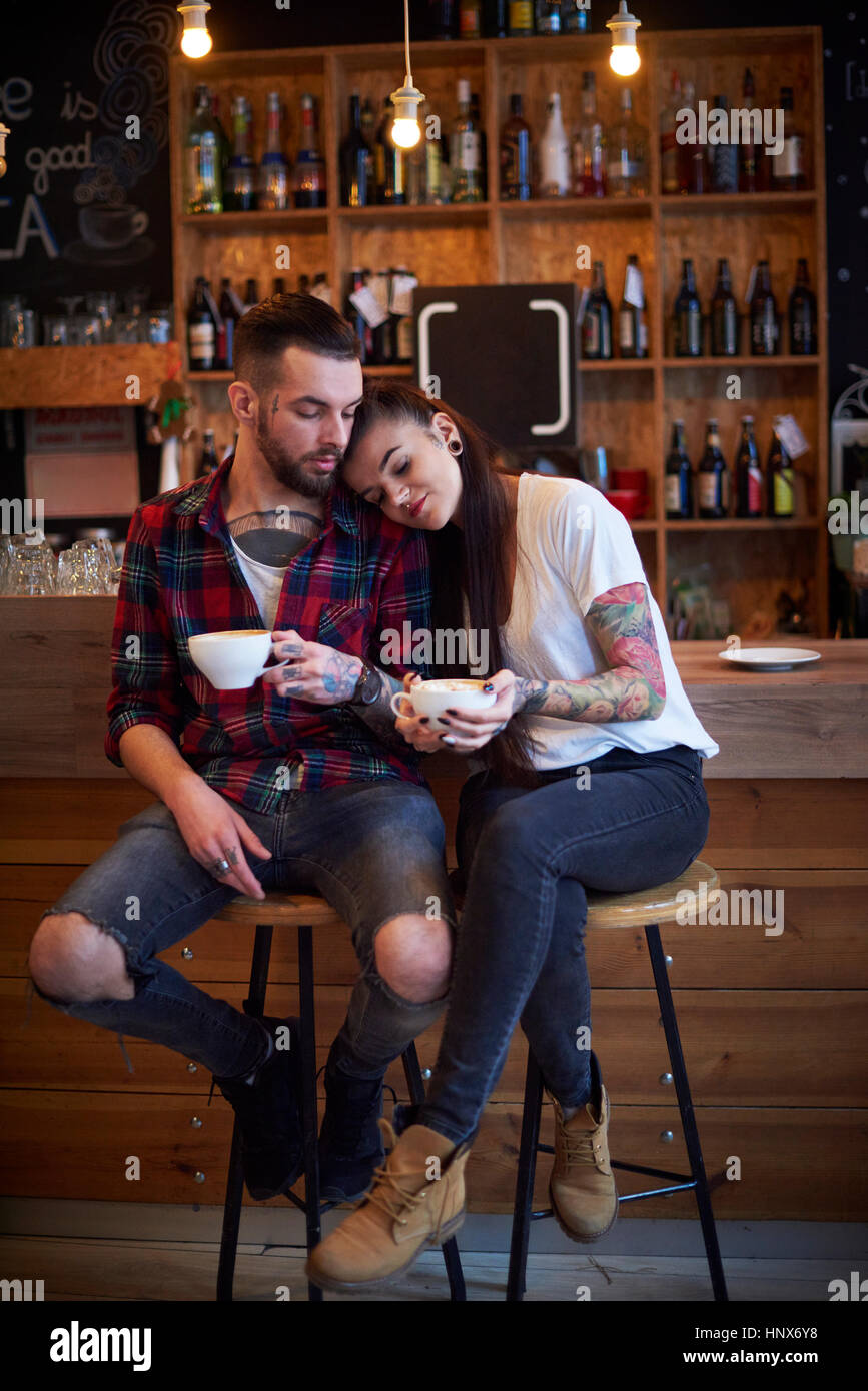 Couple sitting side by side on stools in cafe, head on shoulder - Stock Image