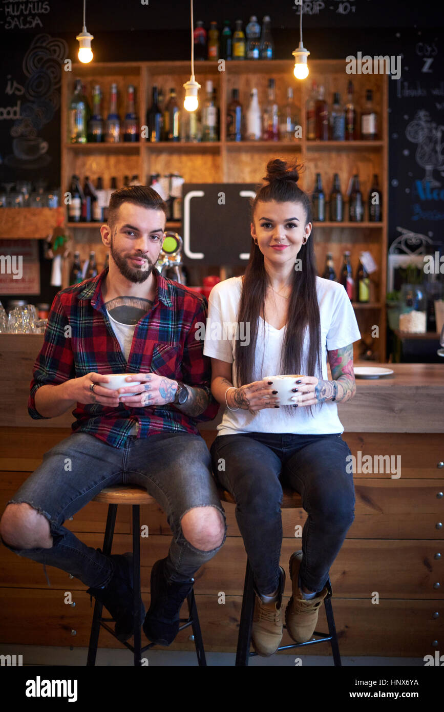 Couple sitting side by side on stools in cafe looking at camera smiling - Stock Image