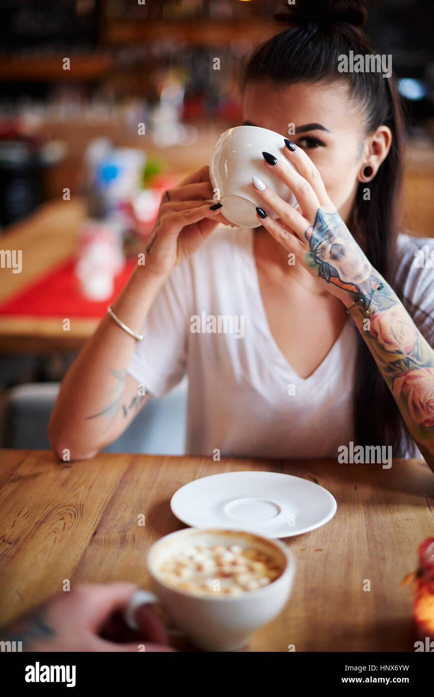 Tattooed woman in cafe drinking coffee looking at camera - Stock Image