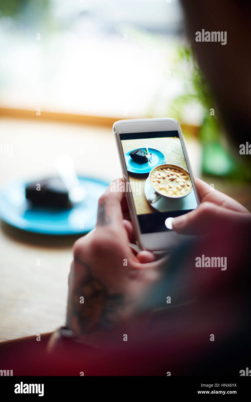 Man taking photo of cake on hot chocolate with smartphone - Stock Image