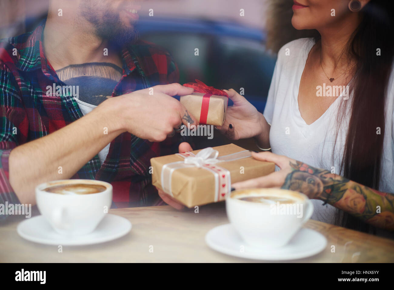 View through window of couple in coffee shop exchanging gifts - Stock Image