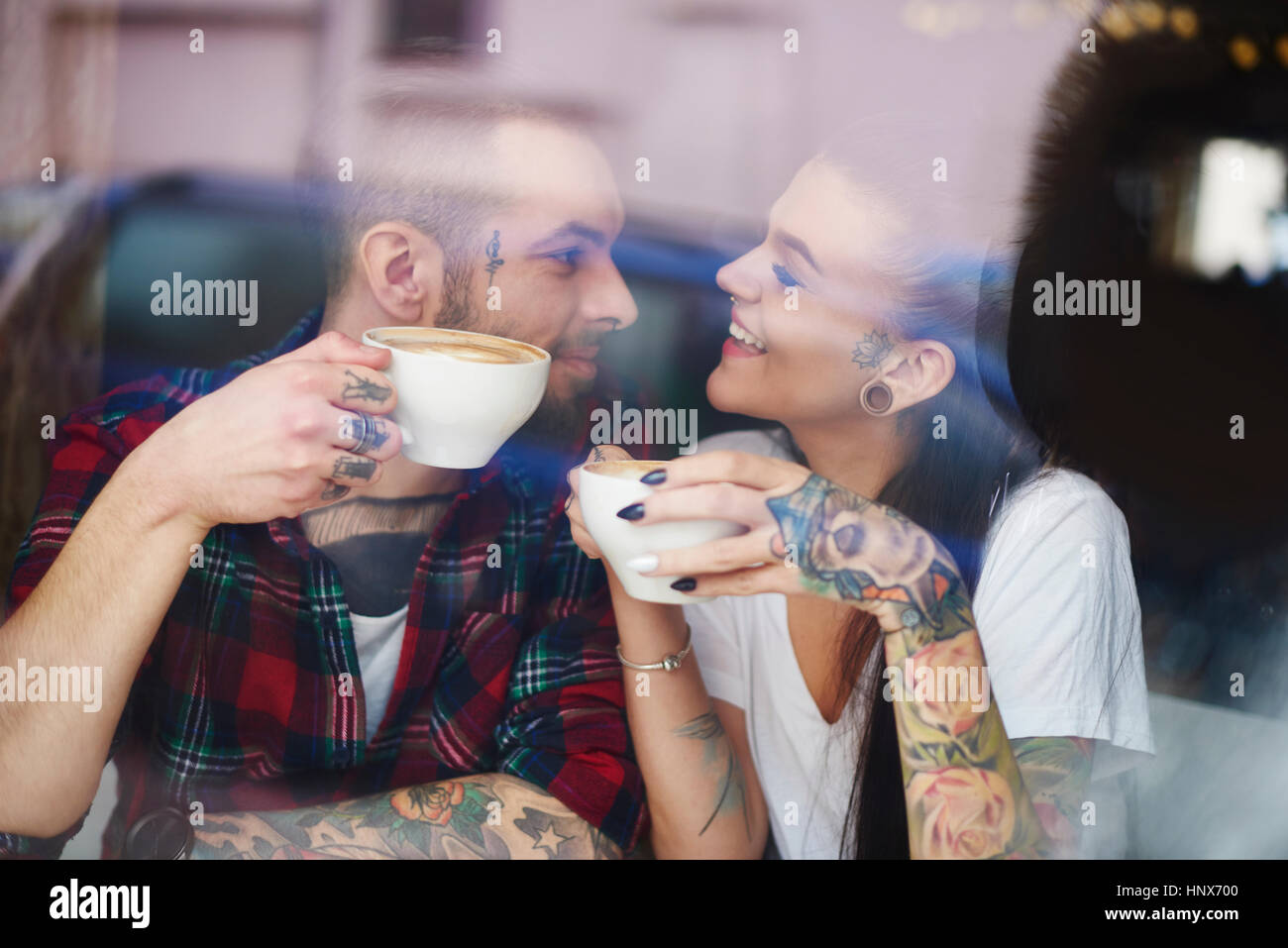 View through window of couple in coffee shop face to face smiling - Stock Image