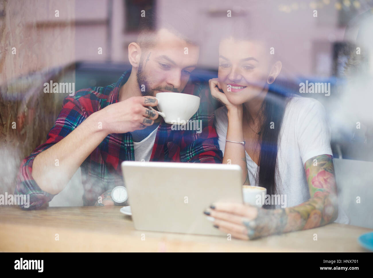 View through window of couple in coffee shop using digital tablet - Stock Image