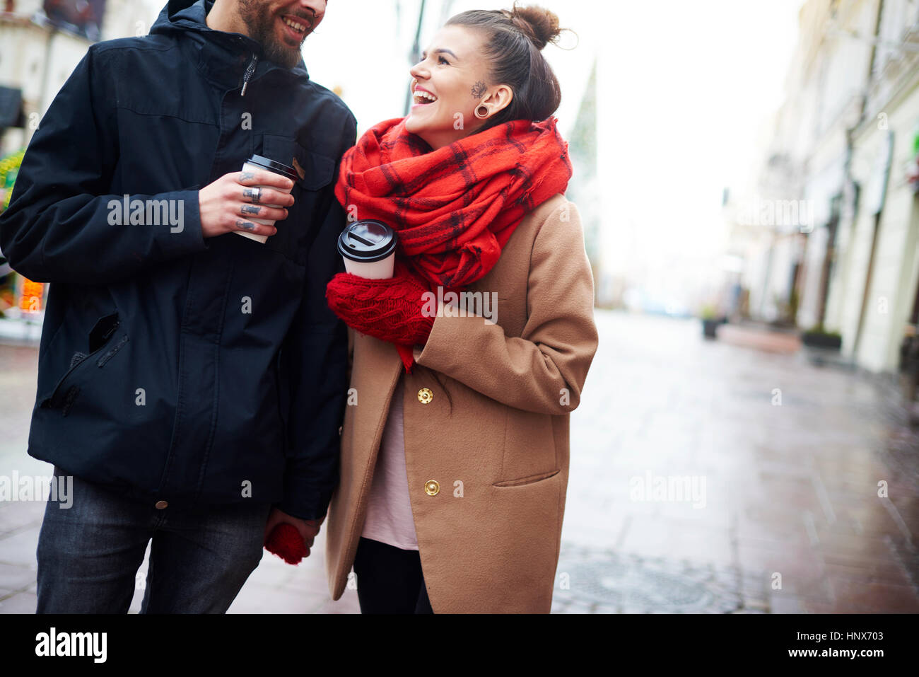 Couple with disposable cups holding hands - Stock Image