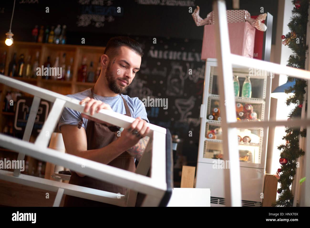 Barista stacking bar stools - Stock Image