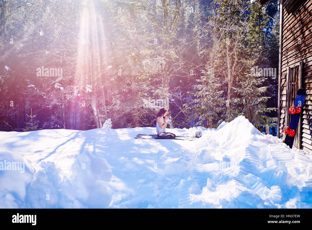 Woman practicing yoga, kneeling on yoga mat by log cabin in snow,  Austria - Stock Image