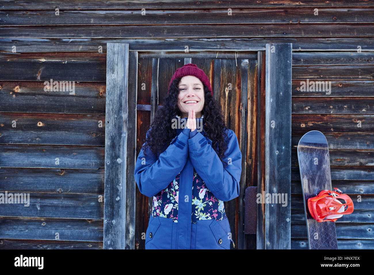 Portrait of woman in knit hat practicing yoga, with hands together by log cabin - Stock Image