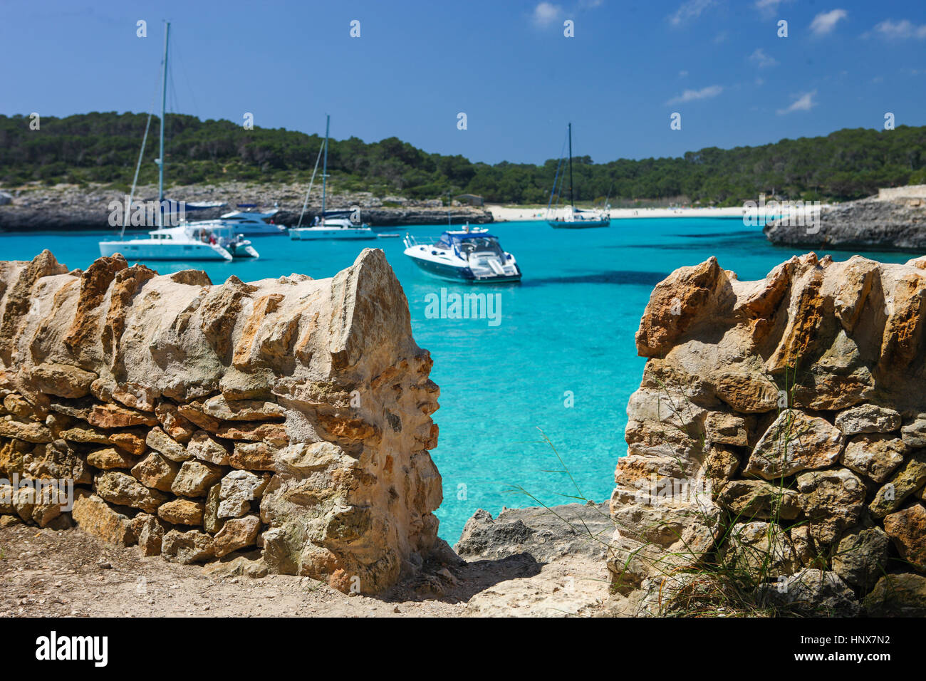 Traditional stone wall and anchored yachts in bay, Majorca, Spain - Stock Image