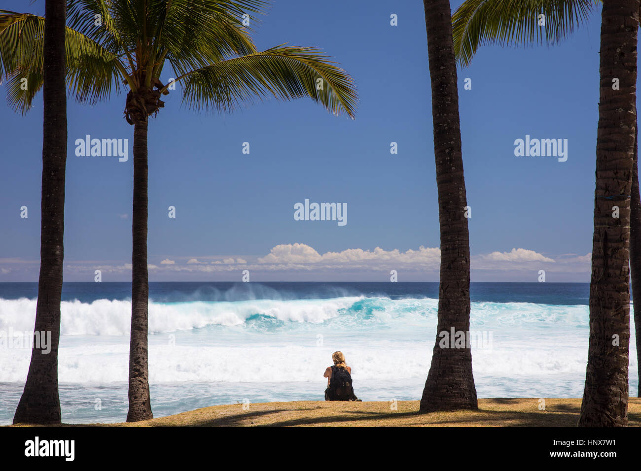 Female tourist sitting on beach looking out at Indian Ocean, Reunion Island - Stock Image